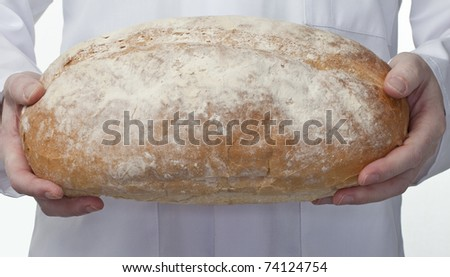 baker holding a freshly baked crusty white loaf of bread - stock photo