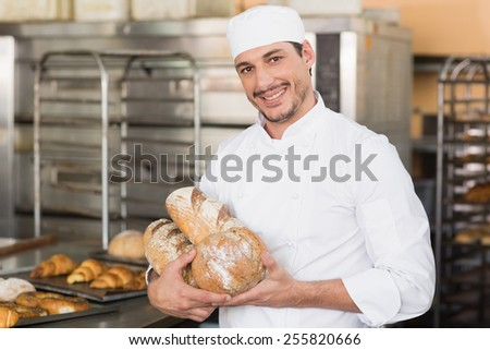 Baker holding freshly baked loaves in the kitchen of the bakery - stock photo