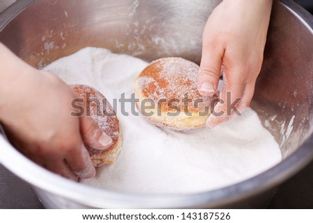 Baker is rolling doughnuts in container with sugar - stock photo