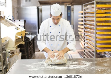 Baker kneading dough in a bakehouse or bakery - stock photo