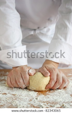 baker making bread , man hands , kneading a dough , cooking coat - stock photo