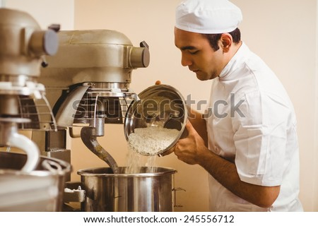 Baker pouring flour into large mixer in a commercial kitchen - stock photo