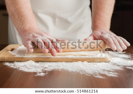 baker rolls out the dough on a wooden kitchen table sprinkled with flour