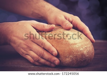 Baker's hands with a bread. Photo with high contrast - stock photo