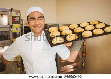 Baker smiling at camera holding tray of rolls in a commercial kitchen - stock photo