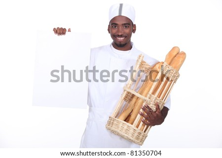 Baker with a basket of baguettes and a board left blank for your message - stock photo