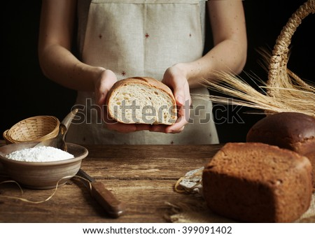 Baker woman holding homemade rustic wheat bread in hands. Selective focus.