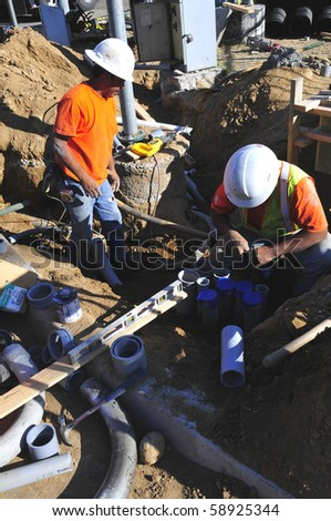 BAKERSFIELD, CA - AUG 12: Electricians completely replace traffic signals, poles and mast arms at a major intersection on August 12, 2010, at Bakersfield, California. Underground conduit is repaired. - stock photo