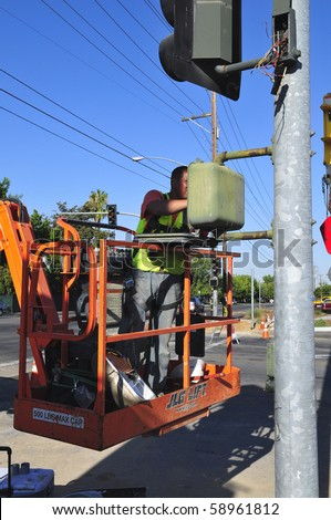 BAKERSFIELD, CA - AUG 12: Electricians completely replace traffic signals, poles and mast arms at a major intersection on August 12, 2010, at Bakersfield, California. - stock photo