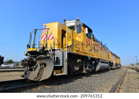 BAKERSFIELD, CA - AUGUST 6,2014: Union Pacific's diesel electric locomotive 623 idles in the switchyard ready to accept a string of boxcars. The route will proceed east into the Sierra Nevada Range. - stock photo