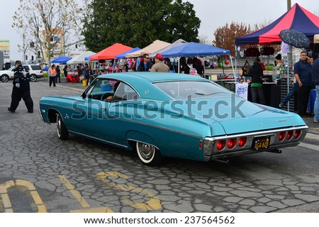 BAKERSFIELD, CA - DECEMBER 13, 2014: A car show entrant is directed to a parking place for his classic Chevy during the Christmas Joy Ride and Toy Run Car Show. - stock photo
