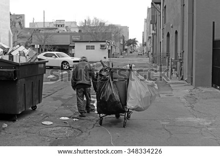BAKERSFIELD, CA - DECEMBER 6, 2015: A homeless man walks the alleys, picking through trash bins, to locate recyclable items to redeem for cash. (monochrome image)