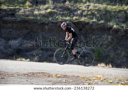 BAKERSFIELD, CA - DECEMBER 6, 2014: An unidentified male contestant starts up a long, steep hill, part of the course of the difficult Hart Park Cyclocross. - stock photo