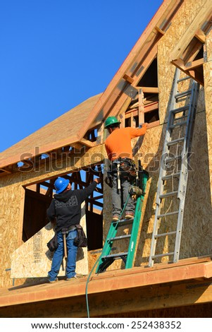 BAKERSFIELD, CA - FEBRUARY 12, 2015: Construction workers apply particle board to the exterior of a two story house, part of the Parkview Cottages low income redevelopment project. - stock photo