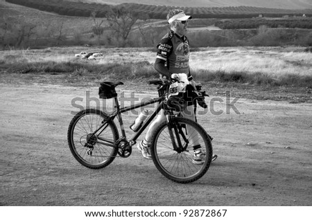 BAKERSFIELD, CA - JAN 14: An unidentified cyclist walks his bike to the start of the Rio Bravo Rumble biathlon (running and mountain biking) on January 14, 2012, in Bakersfield, California. - stock photo
