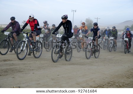 BAKERSFIELD, CA - JAN 14: Cyclists race along the dusty trail at the start of the Rio Bravo Rumble biathlon (running and mountain biking) on January 14, 2012, in Bakersfield, California. - stock photo