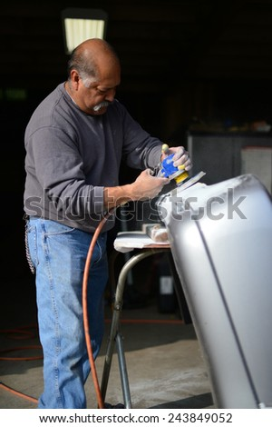 BAKERSFIELD, CA - JAN 13, 2015: Jesse Castenada applies his skill with the sanding wheel to an auto part at a local body shop. - stock photo