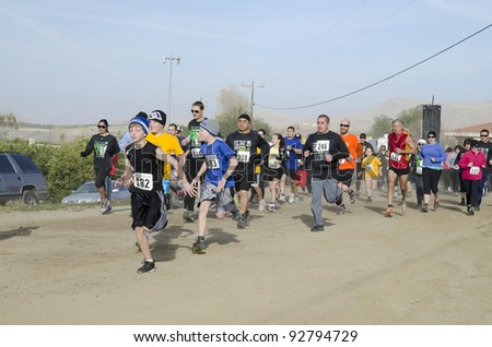 BAKERSFIELD, CA - JAN 14: Men, women and children all run the dirt cross country leg of the Rio Bravo Rumble biathlon (running and mountain biking) on January 14, 2012, in Bakersfield, California. - stock photo