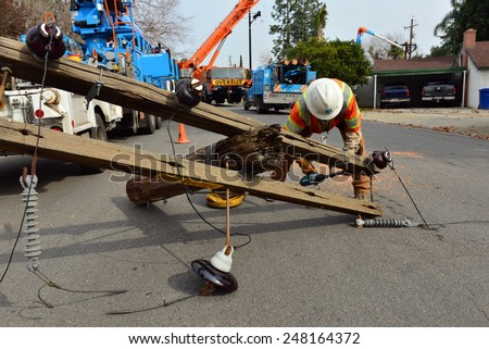 BAKERSFIELD, CA - JANUARY 29, 2015: PG&E employee, Keith Wales, disassembles crossarm hardware from a demolished wood pole that is being replaced. - stock photo