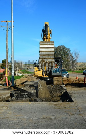 BAKERSFIELD, CA - JANUARY 29, 2016: Power equipment with an articulated boom and ripper teeth demolish road pavement along State Route 178 as new sewer pipe is installed to serve new communities. - stock photo