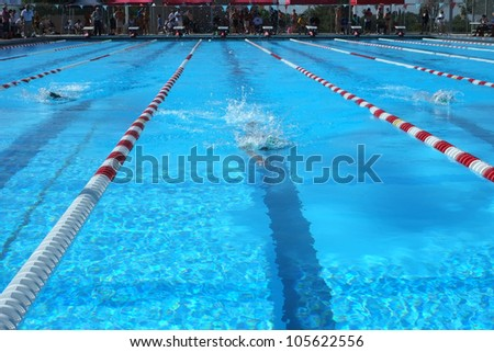 BAKERSFIELD, CA-JUN 9: Unidentified female freestyle swimmers race in their lanes during the Bakersfield Aquatics Club meet on June 9, 2012 at Bakersfield, California. - stock photo