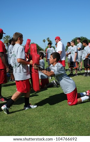 BAKERSFIELD, CA - JUNE 9: Boys learn the fundamentals of the game at the Golden Empire Youth Football Camp at Bakersfield Community College on June 9, 2012,  in Bakersfield, California. - stock photo