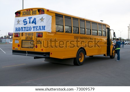 """BAKERSFIELD, CA - MAR 12: The 28th Annual School Bus """"Roadeo"""" tests driver skills on March 12, 2011, in Bakersfield, California. Driver receives instructions from official. - stock photo"""