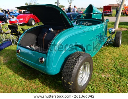 """BAKERSFIELD, CA - MARCH 14, 2015: A colorful Ford-based hot rod roadster is on display at the """"Cruisin' for a Wish"""" classic car show sporting turquoise paint with blue flames. - stock photo"""
