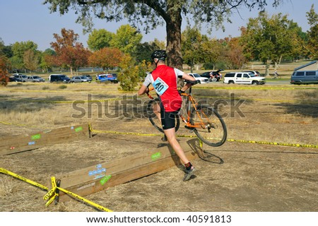 BAKERSFIELD, CA - NOV 7: Contestants dismount, jump barrier and remount during the Fifth Annual Hart Park Cyclocross on November 7, 2009, at Bakersfield, California.