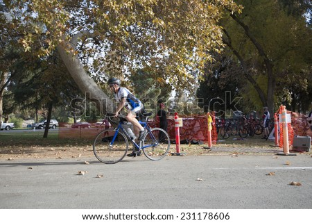BAKERSFIELD, CA - NOVEMBER 16, 2014: An unidentified male contestant emerges from the transition area for the Kern River Duathlon and continues the race on his bicycle. - stock photo