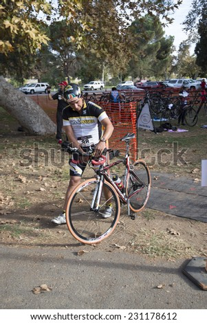 BAKERSFIELD, CA - NOVEMBER 16, 2014: An unidentified male contestant emerges from the transition area for the Kern River Duathlon and continues the race on his bicycle.