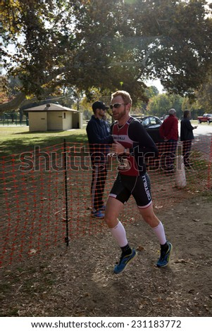 BAKERSFIELD, CA - NOVEMBER 16, 2014: An unidentified male contestant ends his run into the transition area for the Kern River Duathlon to continue the race on his bicycle. - stock photo