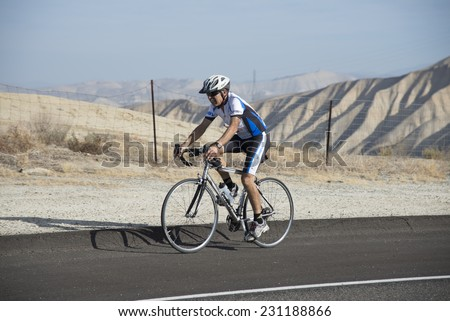 BAKERSFIELD, CA - NOVEMBER 16, 2014: An unidentified male contestant has completed a run and now speeds over the course during  the cycling portion of the Kern River Duathlon. - stock photo