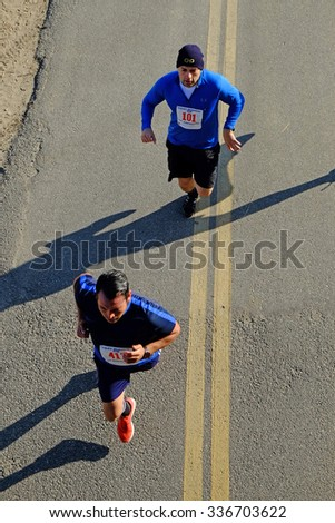 BAKERSFIELD, CA - NOVEMBER 7, 2015: Two contestants present an unusual top view as they run under an overpass during the 33rd Annual Bakersfield Police Department Memorial Run.
