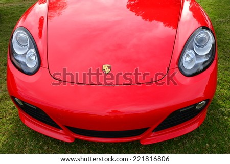 BAKERSFIELD, CA - OCTOBER 4, 2014: Greg Fullmer's 2012 bright red Porsche Cayman shows off it's smooth contours, ready for judging, at this year's Concours D'Elegance.  - stock photo