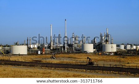 BAKERSFIELD, CA - SEPTEMBER 5, 2015: Producing oil wells crowd against the boundaries of a refinery. Production and refining are one of Kern County's major industries. - stock photo