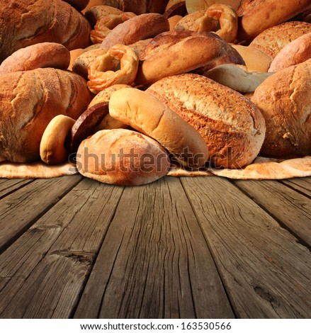 Bakery bread  food concept on an old fashioned wood table background with a group of baked goods made from whole wheat and natural grains as pumpernickel pita focaccia bagel and french baguette. - stock photo