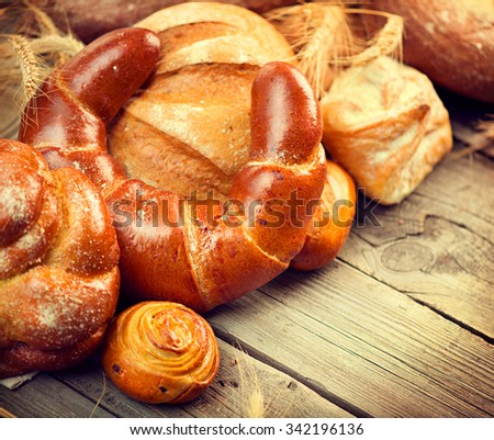 Bakery Bread on a Wooden Table. Various Bread and Wheat Ears Still-life - stock photo