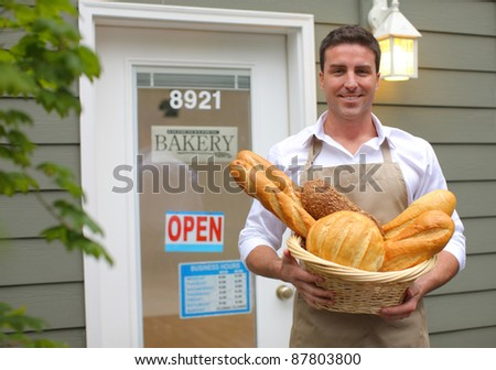 Bakery owner in front of shop with bread - stock photo