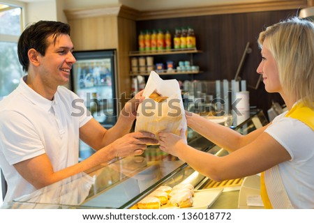 Bakery shopkeeper gives pastry to customer - stock photo