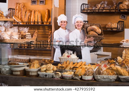 Bakery staff offering bread and different pastry for sale in interior - stock photo