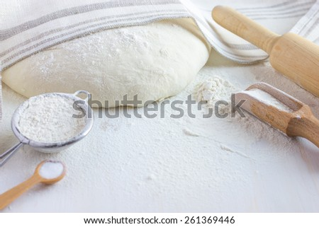 baking background.  Flour, bake ware and  dough on white wooden table