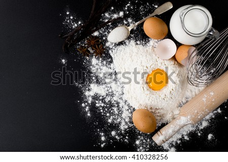 baking background with cake ingredients on black chalkboard from above bowl flour eggs - stock photo