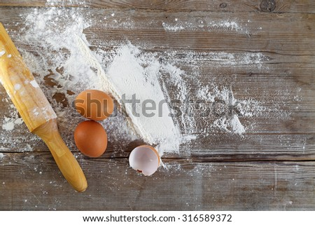 Baking background with eggs, eggshells, flour and rolling pin. - stock photo