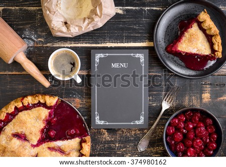 Baking background with sliced cherry pie, flour, rolling pin and menu chalkboard on the black wooden table. Ingredients for baking/dessert or pie making - stock photo