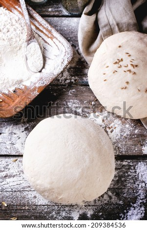 Baking bread. Dough on wooden table with flour, rolling-pin and jars with backing ingredients. Top view.  - stock photo