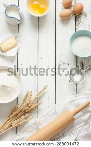 Baking cake in rustic kitchen - dough recipe ingredients (eggs, flour, milk, butter, sugar) on white planked wooden table from above. Background layout with free text space. - stock photo