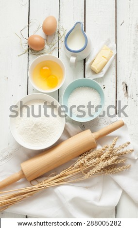 Baking cake in rustic kitchen - dough recipe ingredients (eggs, flour, milk, butter, sugar) on white planked wooden table from above. - stock photo