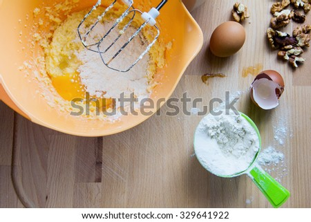 Baking cake ingredients. Bowl, flour, eggs and nuts on the wood desk. - stock photo