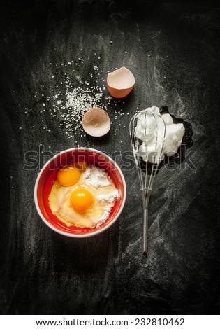 Baking cake ingredients - bowl, flour, eggs, egg whites foam, eggbeater and eggshells on black chalkboard from above. Cooking course poster concept - layout with free text space. - stock photo